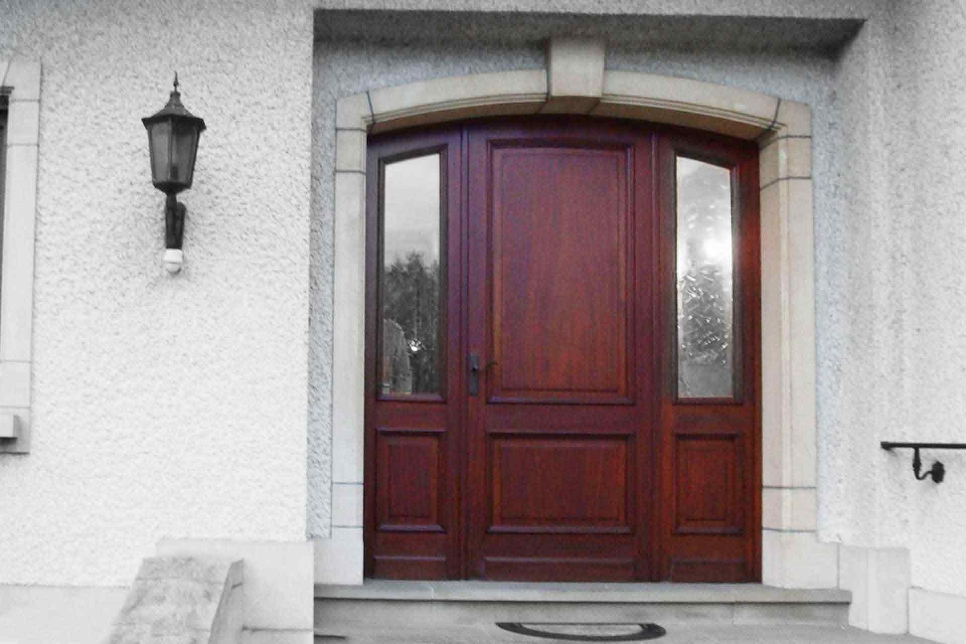 Vorher-Bild. Vor der Modernisierung mit Coplaning Luxemburg. Nahaufnahme des Eingangsbereichs eines weißen Einfamilienhauses mit Blick auf die neue braune Coplaning Haustür.
