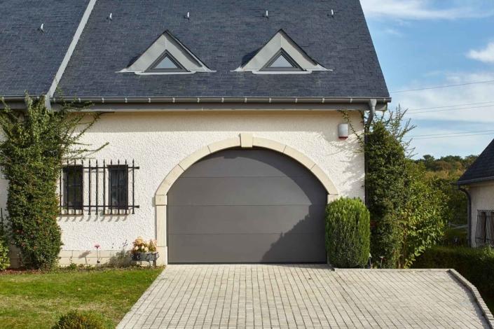Rechte Seite der Vorderseite eines weißen Einfamilienhauses mit Blick auf ein graues Coplaning Alu Garagentor.