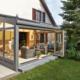 Weißes Einfamilienhaus mit einem grauen klimatisiertem Coplaning Holz- Alu Veranda Wintergarten mit Außenmarkise.