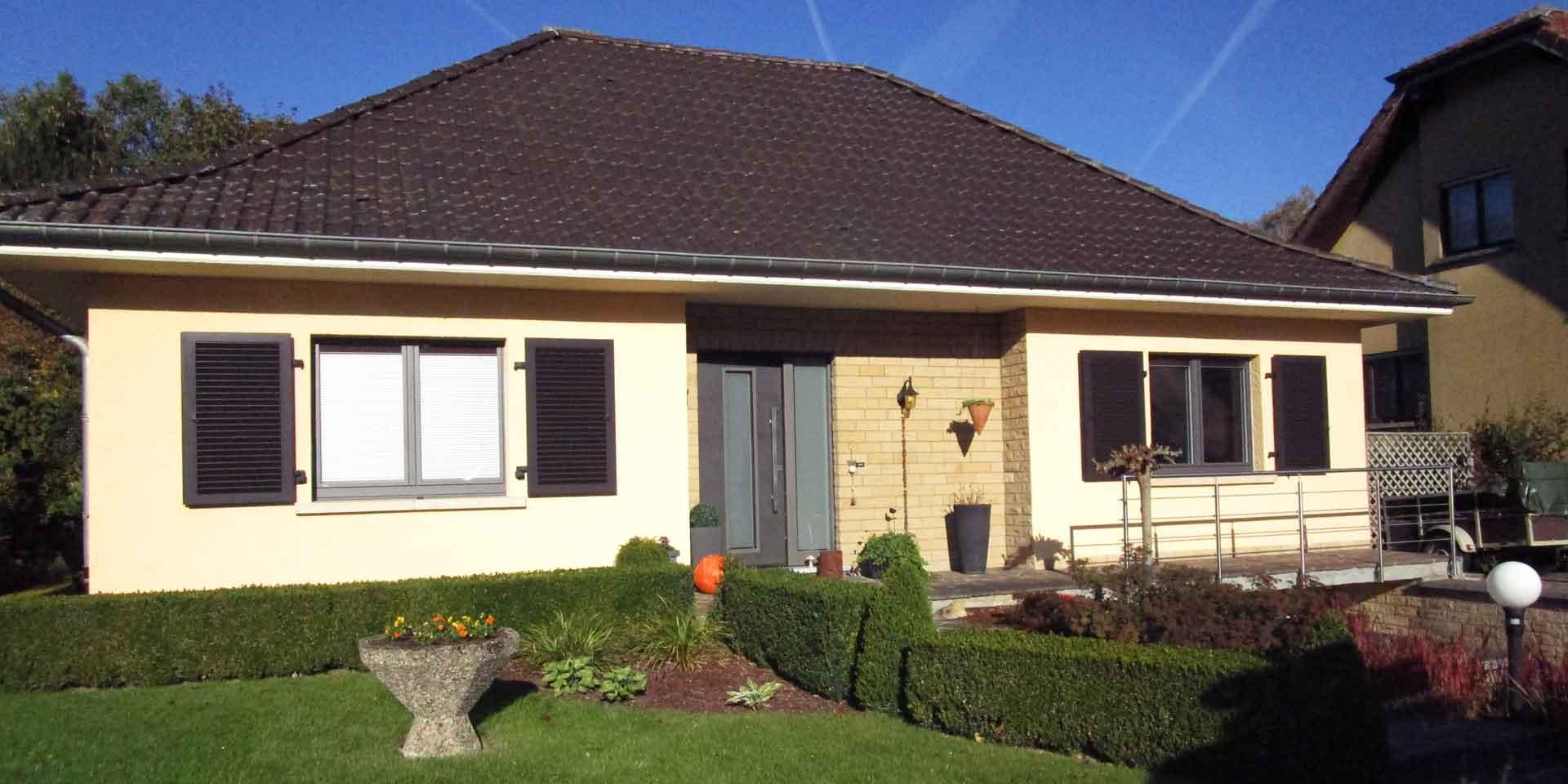 Gelbliches Einfamilienhaus mit einer modernen grauen Coplaning Keramik Haustür und braunen Coplaning Holz Jalousienfenster.