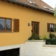 Oranges Einfamilienhaus mit einer brauner Coplaning Haustür mit Glasausschnitten.