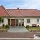 Weißes Einfamilienhaus in Ehnen mit moderner Alu braunen Coplaning Haustür und braunen Coplaning Alu Fenster mit integrierten Jalousien.