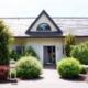 Weißes Einfamilienhaus mit grauer Coplaning Alu Haustür und darüber ein Coplaning Alu Halbkreis Fenster.