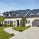 Weißes Einfamilienhaus mit grauer Coplaning Keramik Haustür, braunen Coplaning Holz- Alu Fenster und einem grauen Deckensektionalen Garagentor.