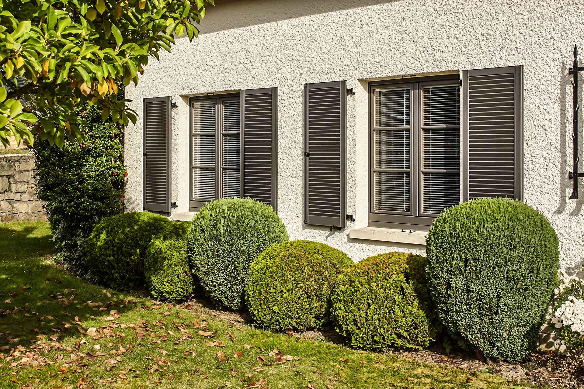 Nahaufnahme der linken Vorderseite des weißen Einfamilienhauses mit Blick auf braune Coplaning Holz- Alu Fenster mit Sprossen und Klappläden.