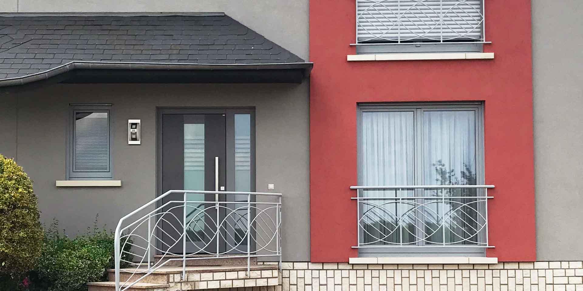Nahaufnahme der Vorderseite eines grau- roten Einfamilienhauses mit einer grauen Coplaning Keramik Haustür.