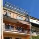 Oranges Einfamilienhaus mit einer grauen Coplaning Alu Balkon Überdachung mit Glasdach.