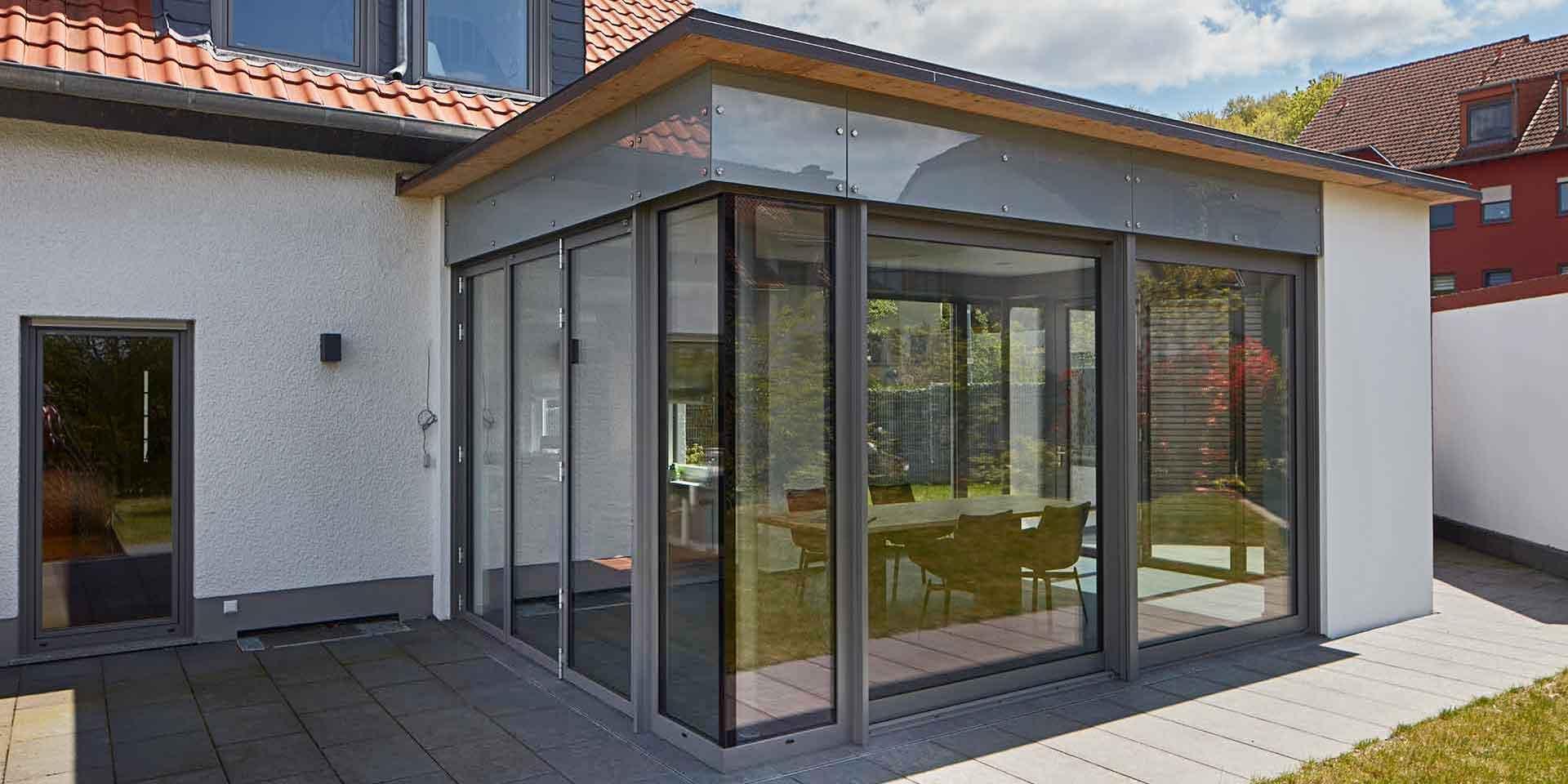 Weißes Einfamilienhaus mit einem grauen Aluminium Coplaning Veranda Anbau mit Faltanlage, Glasfaltwand und Ganzglasecken.