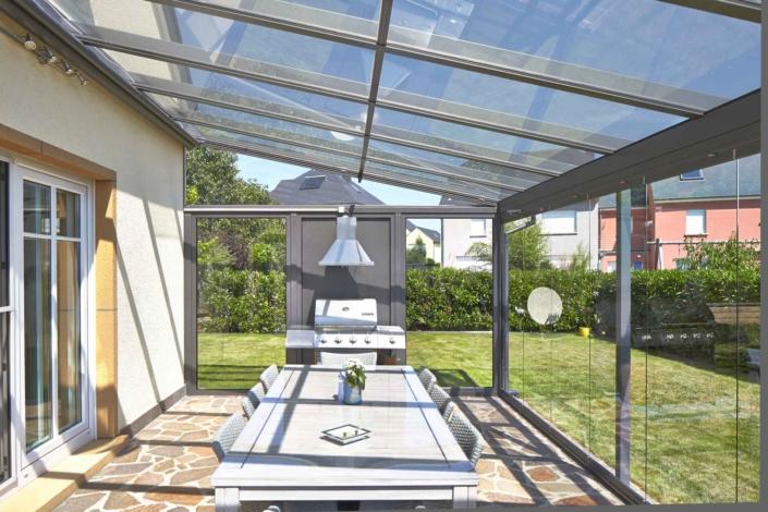 Gelbes Einfamilienhaus mit einer Coplaning Veranda Terassenüberdachung mit Alumiumprofilen und einer geschlossenen grauen Coplaning Glasfaltwand.