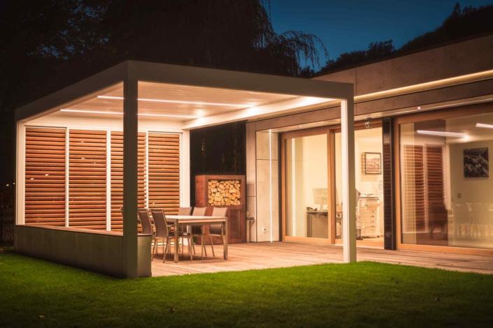 Modernes Einfamilienhaus mit einem hochwertigen Coplaning Pergola in der Nacht mit moderner Terassenüberdachung eind einem Quadrato in weiß mit Lamellendach.