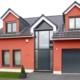 Rotes Einfamilienhaus mit grauer moderner Coplaning Haustür und grauen Coplaning Holz- Alu Fenster.