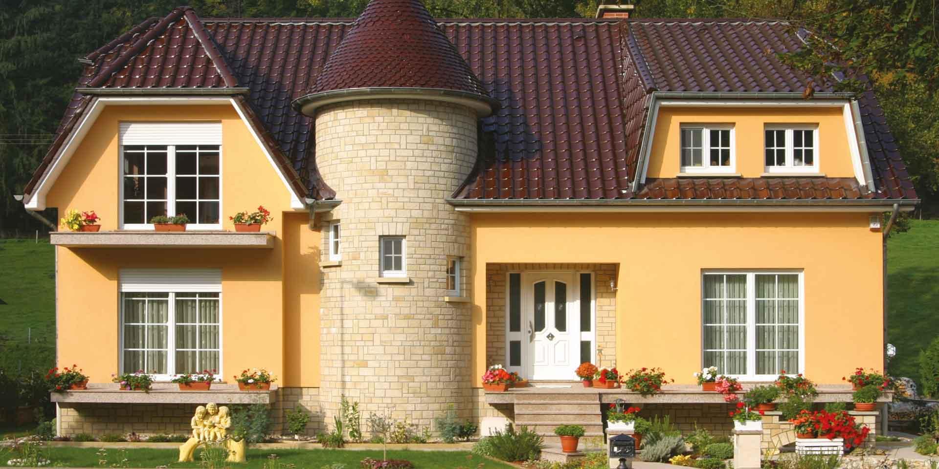 Gelbes Einfamilienhaus mit klassisch weißer Coplaning Haustür und großen weißen Coplaning Fenster.