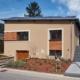 Braunes Einfamilienhaus mit modernen braunen Coplaning Alu Fenster und einem Coplaning Garagentor aus Holz.