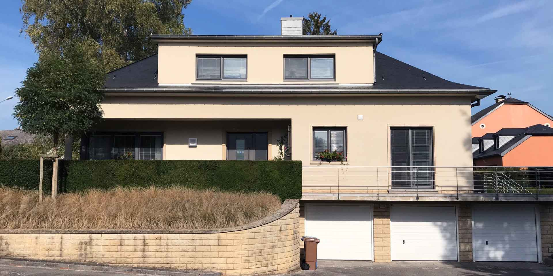 Beiges Einfamilienhaus mit grauen Coplaning PVC Alu-Fenster und einer grauen modernen Coplaning Haustür mit Seitenlicht aus Glas.
