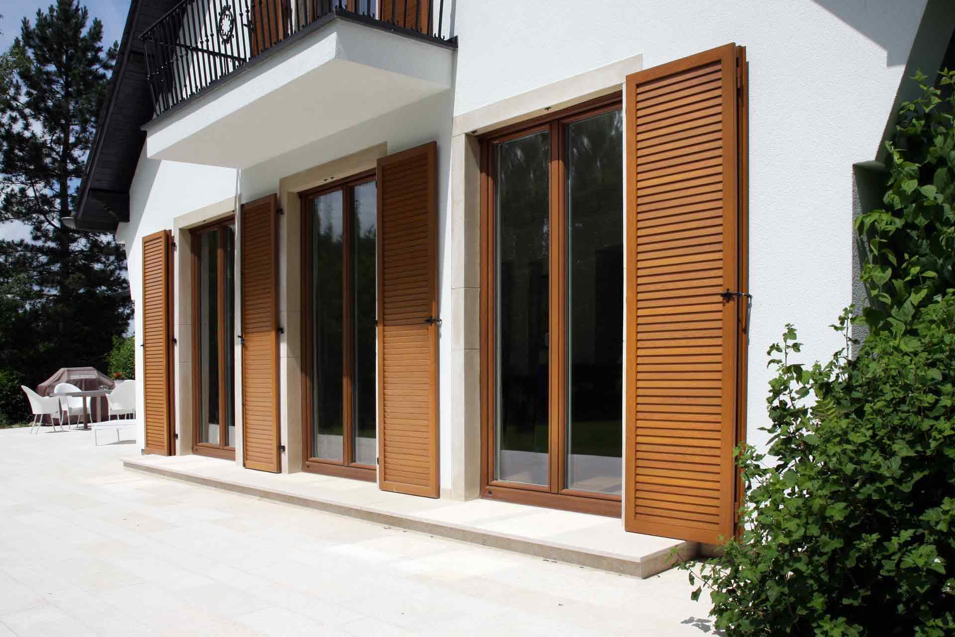 Großes weißes Einfamilienhaus mit Nahaufnahme auf Rückseite des Hauses mit Blick auf drei Coplaning Fenstertüren mit Klappläden aus Holz.