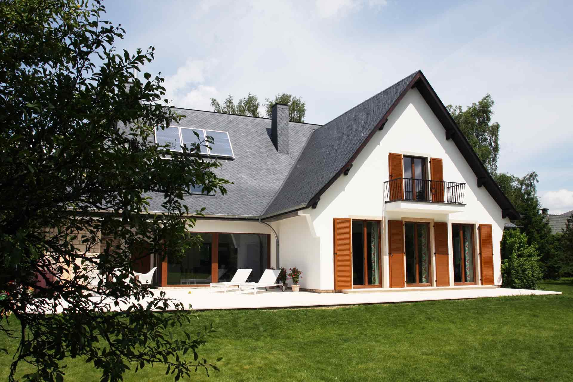 Rückseite von links gesehen man sieht ein großes weißes Haus mit Coplaning Holzfenster und Fenstertüren mit Klappläden aus Holz mit integrierten Jalousien.