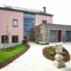 Pinkes Einfamilienhaus in Nocher mit einer rot- grauen Coplaning Haustür, grauen Coplaning Alu Fenster und zwei rot- grauen Coplaning Alu Garagentoren.