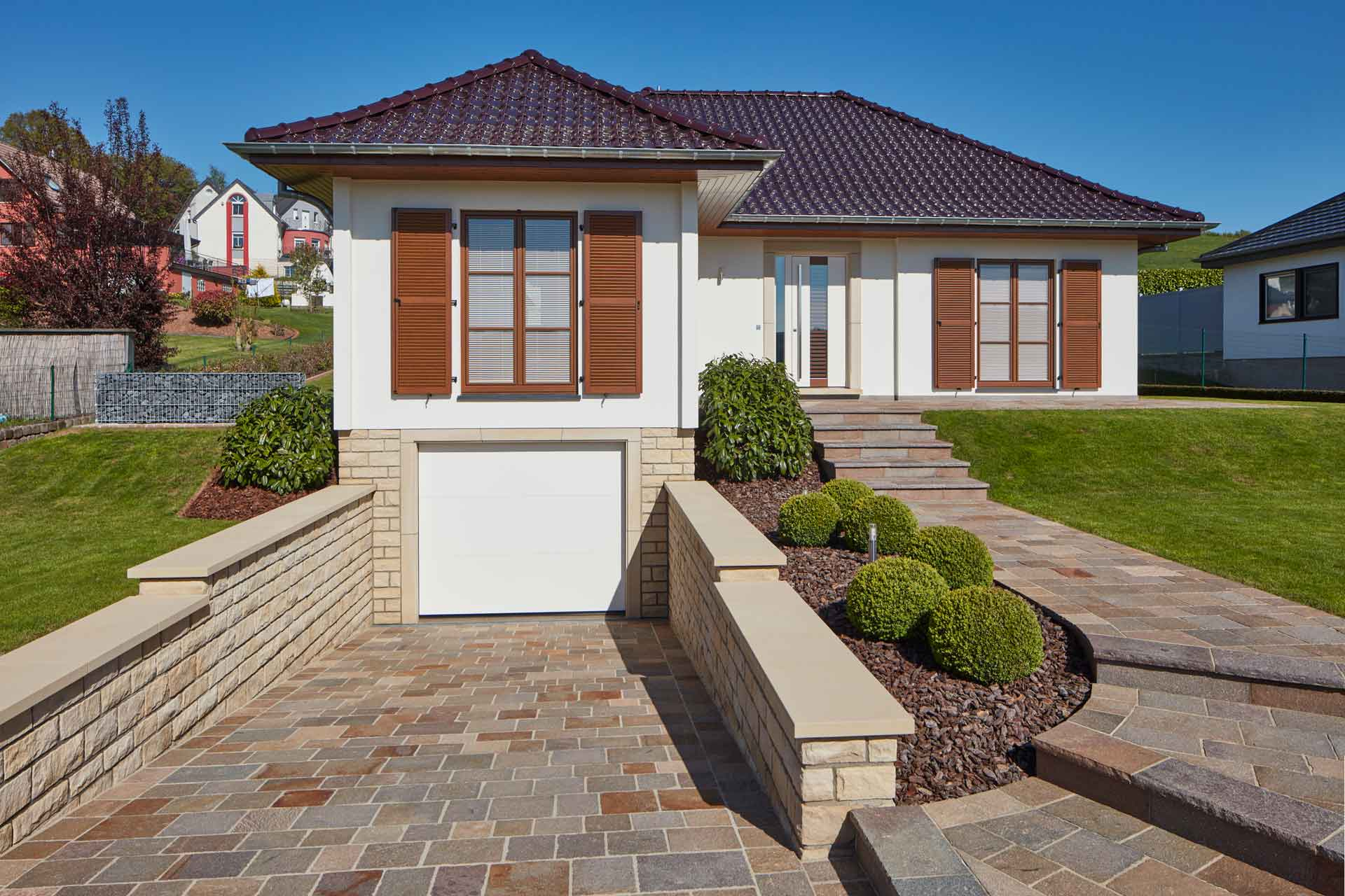 Weißes Einfamilienhaus mit einer weiß- braunen Haustür, braunen Coplaning Jalousiefenster mit passenden Klappläden und einem weißen Coplaning Garagentor.