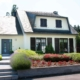 Weißes Einfamilienhaus mit braunen Coplaning Alu Fenster mit passenden Klappläden und einer grauen Coplaning Alu Haustür.