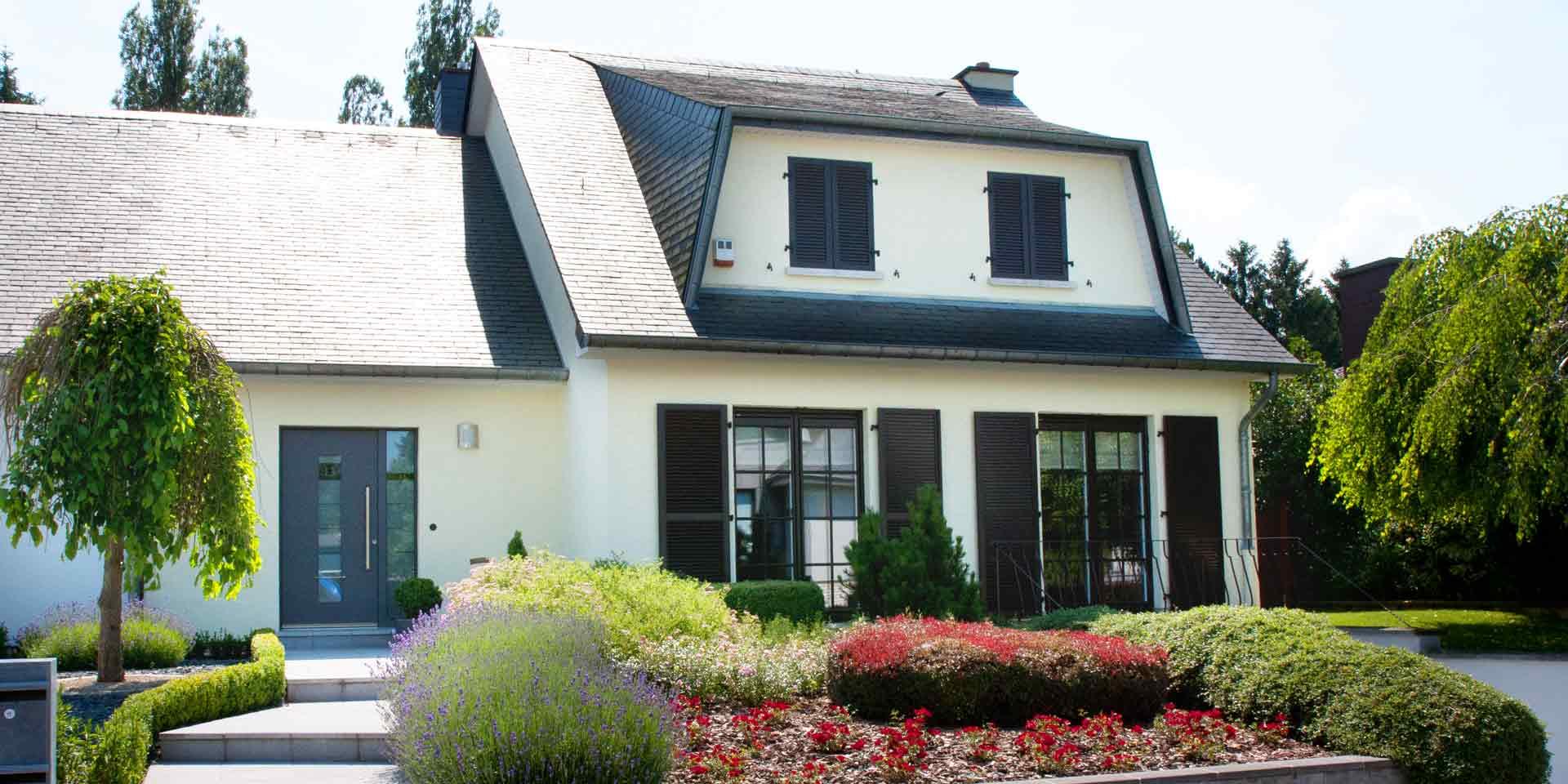 Weißes Einfamilienhaus mit grauen Coplaning Alu Fenster mit passenden Klappläden und einer grauen Coplaning Alu Haustür.
