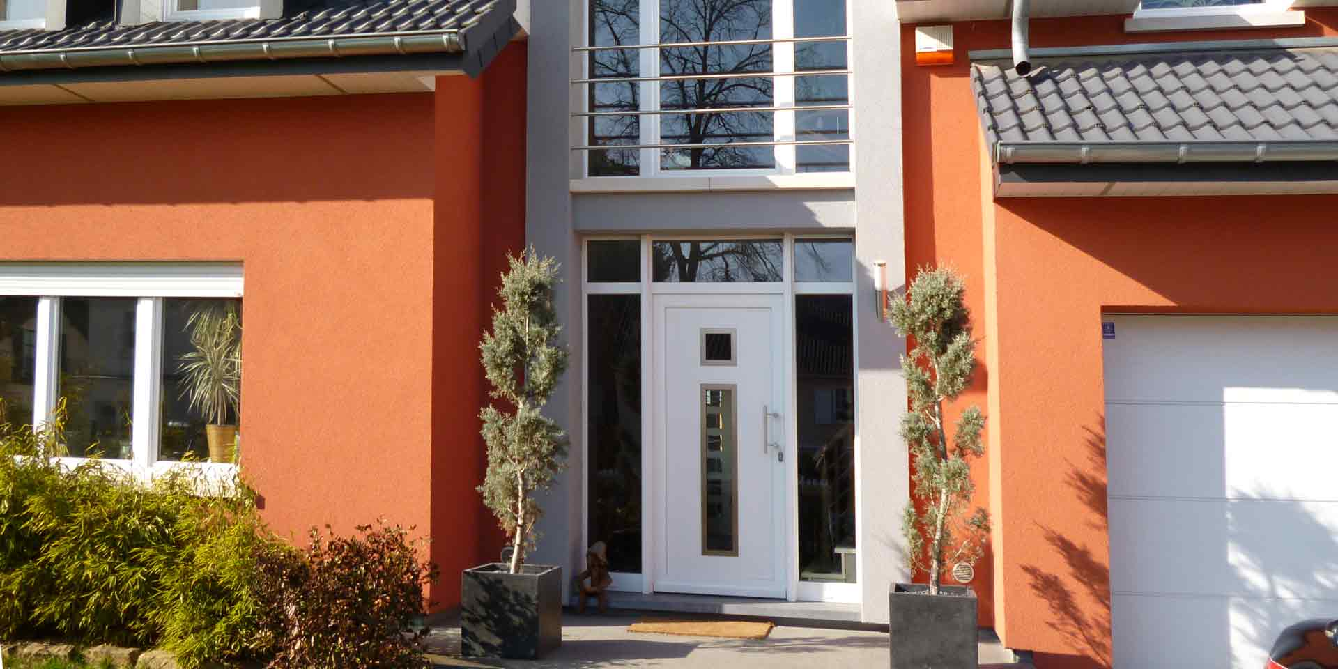 Nahaufnahme des Eingangsbereichs eines roten Einfamilienhauses mit Blick auf eine weiße moderne Coplaning Haustür mit Glas und darüber ein großes weißes Coplaning Gauben- Kunststoff Fenster.