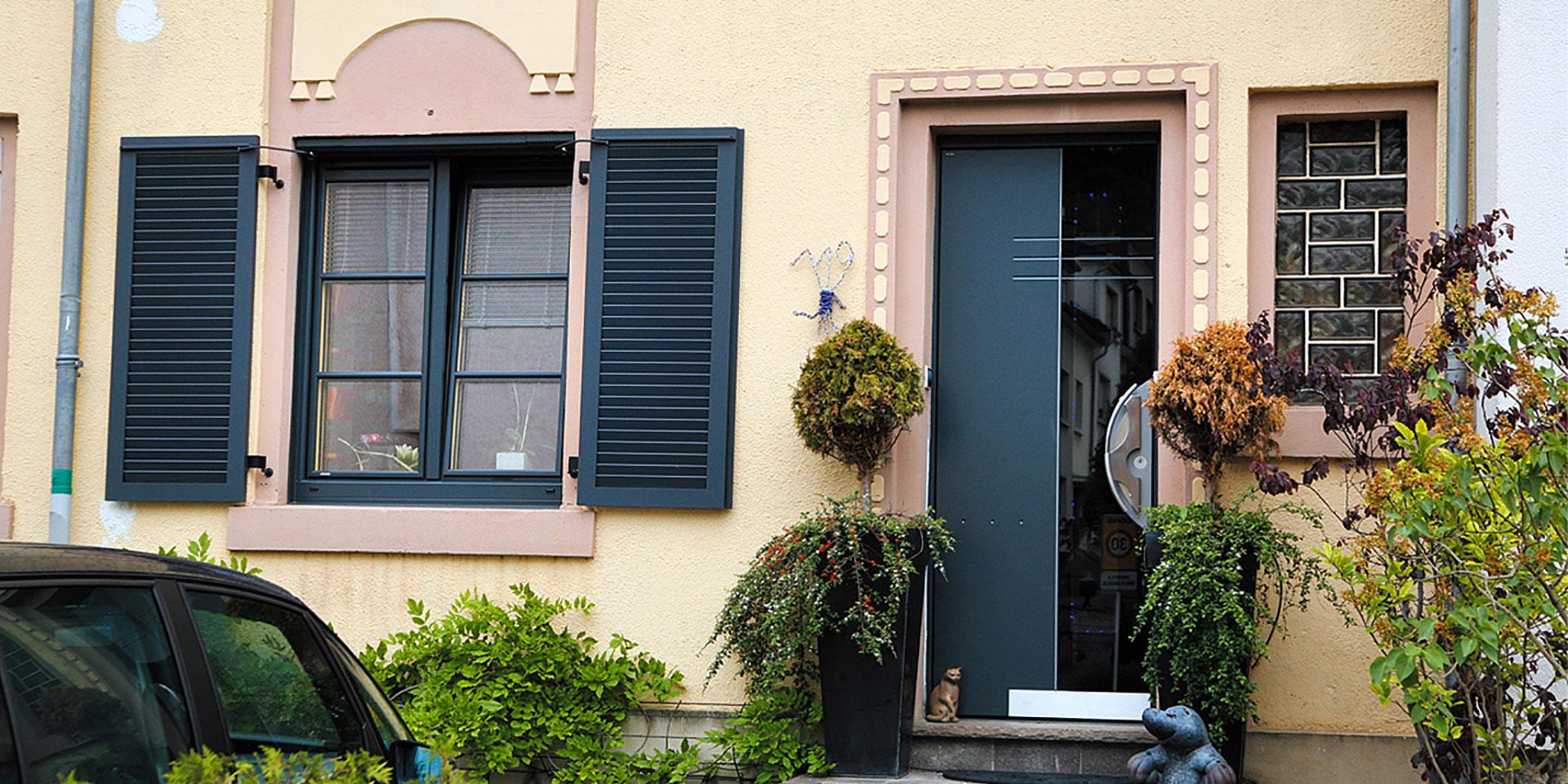 Gelbes Einfamilienhaus mit Nahaufnahme des Eingangsbereichs mit Blick auf eine graue Coplaning Aluminium Haustür und grauen Coplaning Kunststoff Fenster mit grauen Aluminium Klappläden.