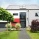 Rot- grau- weißes Einfamilienhaus mit moderner grauer Coplaning Haustür, grauen Coplaning Alu Fenster und einem grauen Coplaning Garagentor.