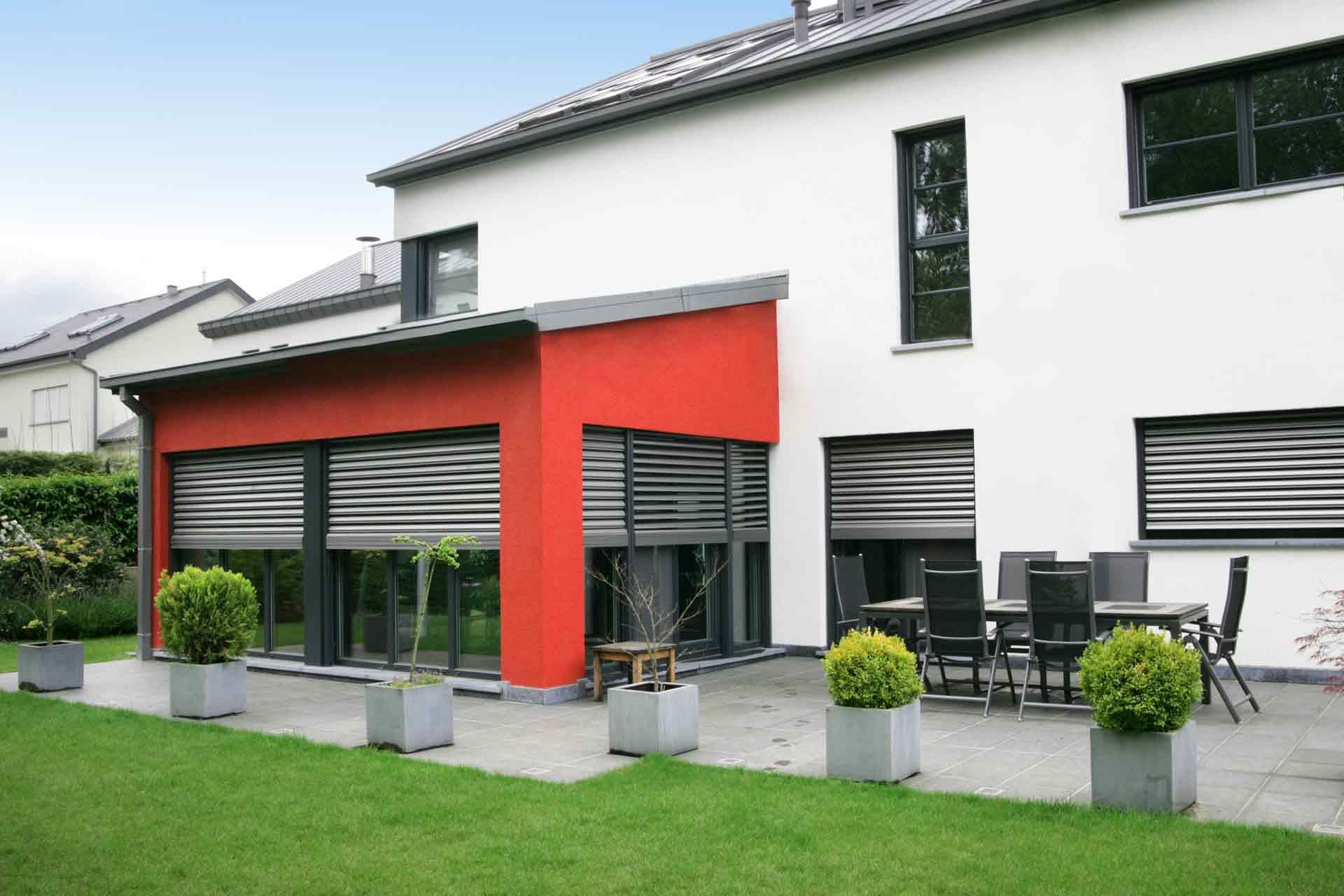 Rückseite des rot- grau- weißen Einfamilienhauses mit Blick auf die grauen Coplaning Alu Fenster.