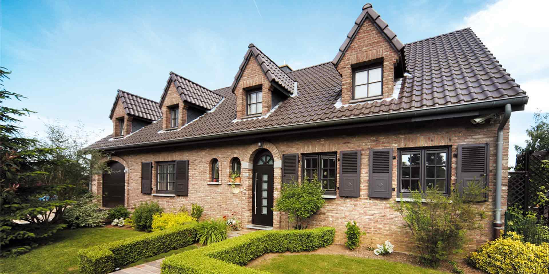 Einfamilienhaus mit Steinfassade mit brauner Coplaning Rundbogen Haustür und brauen Landhausstil klassischen einbruchsicheren Coplaning Gaubenfenster.