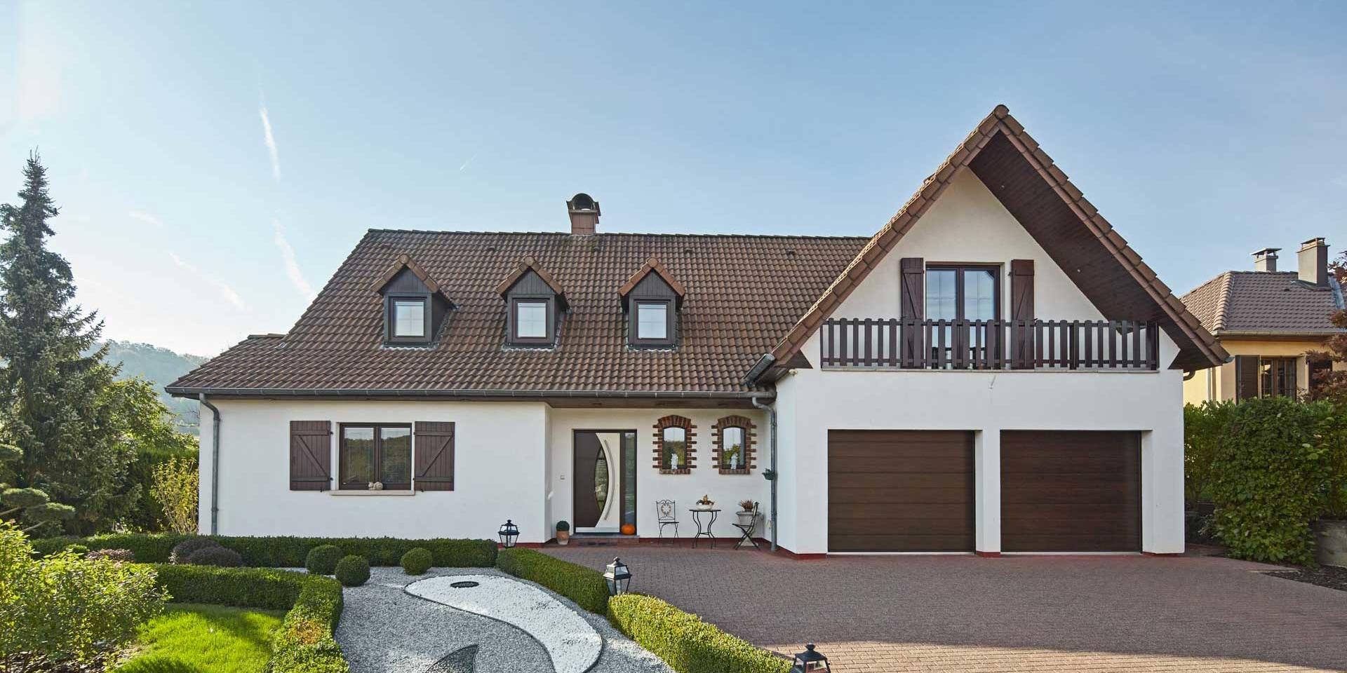 Großes weißes Einfamilienhaus mit einer modernen braun- weißen Haustür und braunen Fenster