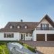 Großes weißes Einfamilienhaus mit einer modernen braun-weißen Coplaning Haustür und braunen Coplaning Holz-Alu Fenster mit integrierten Jalousien