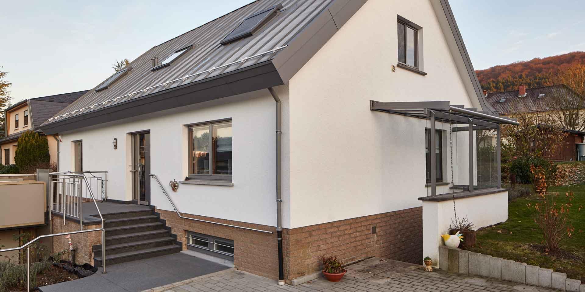 Weißes Einfamilienhaus von rechts gesehen mit einer neuen modernen grauen Coplaning Haustür und grauen Coplaning Holz Alu Fenster.