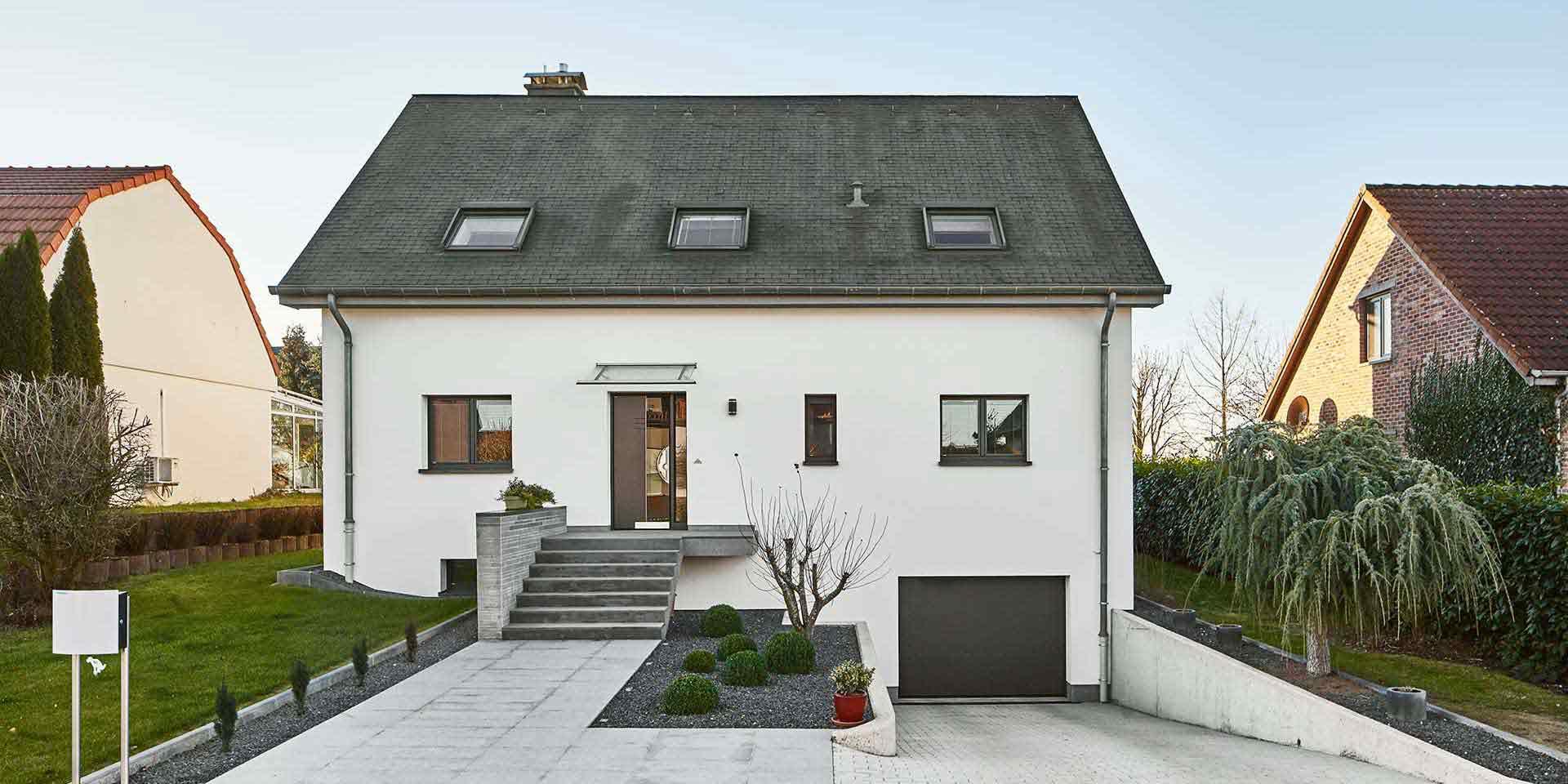 Weißes Einfamilienhaus mit einer grauen Coplaning Haustür, grauen einbruchsicheren Coplaning Alu Fenster und einem grauen Garagentor.