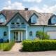 Blaues Einfamilienhaus mit weißer Coplaning Haustür und weißen Coplaning runden Fenster.
