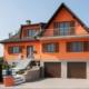 Rotes Einfamilienhaus mit grau- brauner Coplaning Haustür und braunen Coplaning Fenster mit Klappläden und zwei braunen Garagentor.