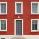 Nahaufnahme der Vorderseite des roten Einfamilienhauses mit grauer Coplaning Haustür mit Glasauschnitten und mit weißen Coplaning Fenster.