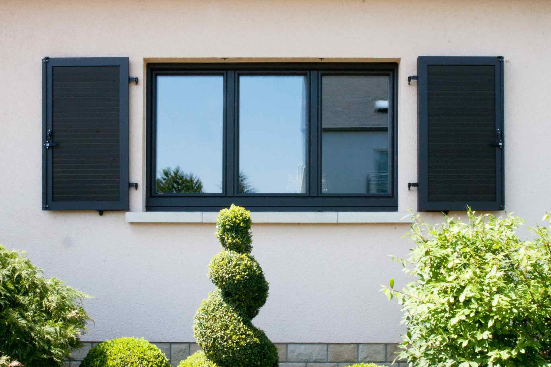 Nahaufnahme von einem modernen grauen Coplaning Fenster mit grauen Klappläden des leicht pinken Einfamilienhauses.