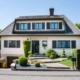 Leicht pinkes Einfamilienhaus mit moderner grau- schwarzen Coplaning Haustür,grauen Coplaning Fenster mit grauen Klappläden und mit einem Garagentor.