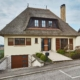 Weißes Einfamilienhaus mit Coplaning Holz- Glas Haustür, Coplaning Holz- Alu Fenster und ein Garagentor mit Holzoptik.