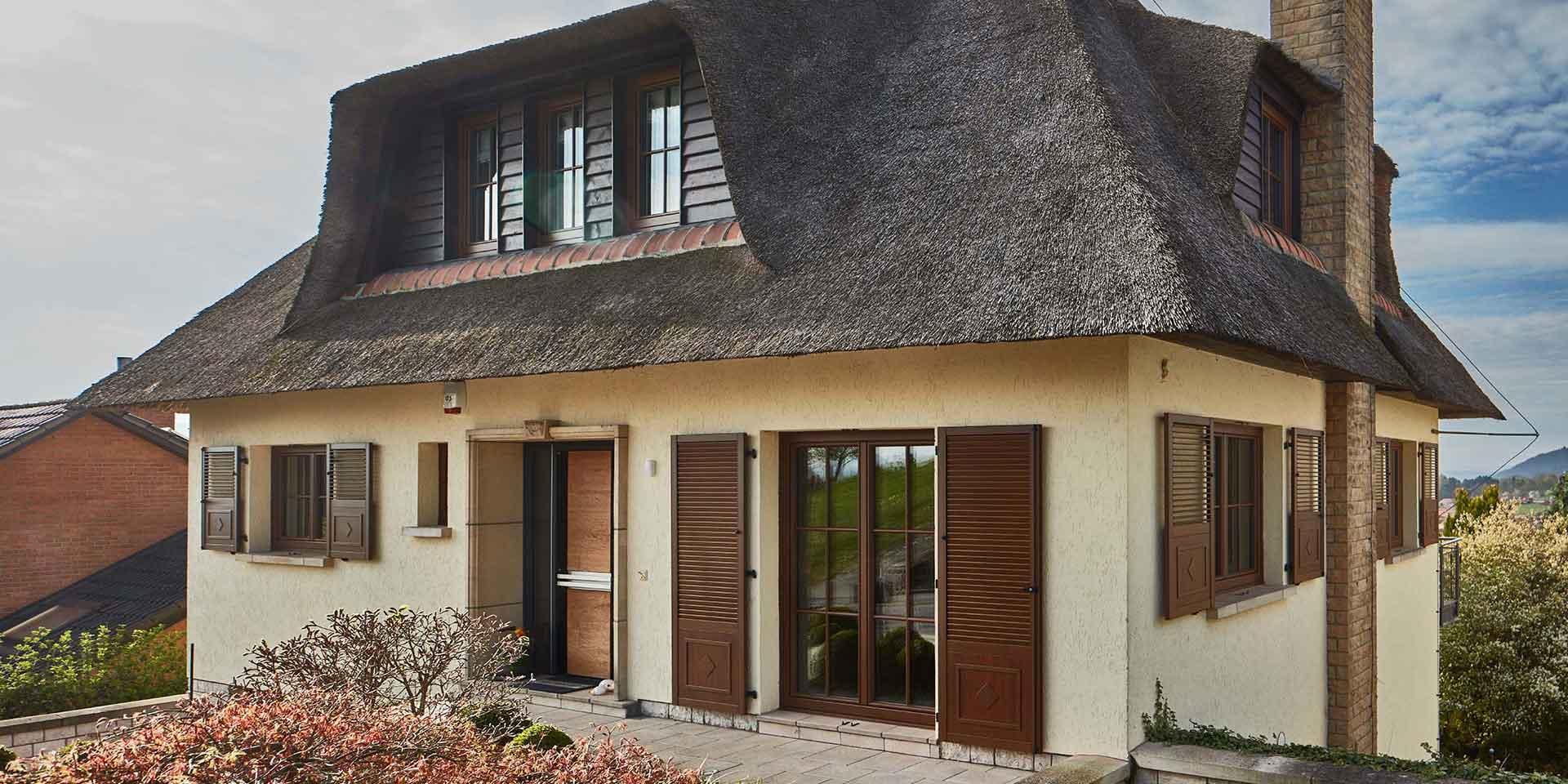 Weißes Einfamilienhaus von rechts gesehen mit moderner Coplaning Holz- Glas Haustür und Coplaning Holz- Alu Fenster.