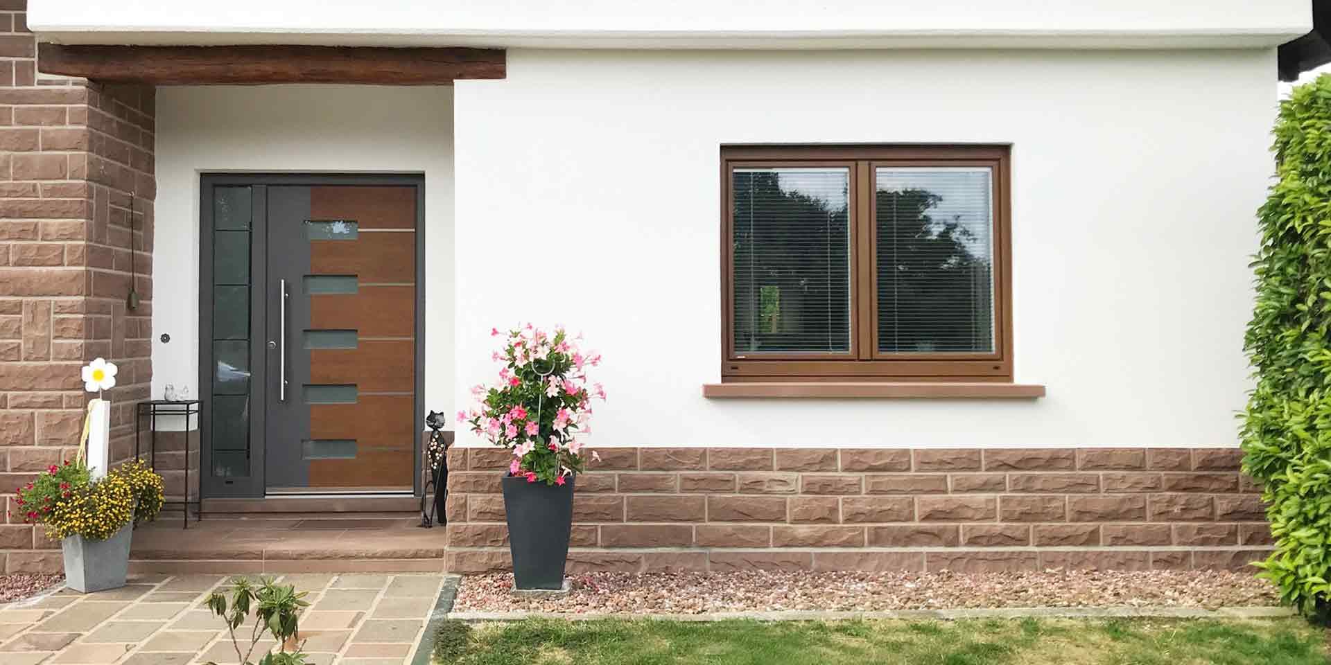 Nahaufnahme der Vorderseite des weiß-braunen Einfamilienhauses mit der modernen grau-braunen Coplaning Haustür links im Bild und dem Alu Holz Coplaning Fenster rechts im Bild.