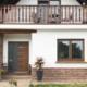 Weiß- braunes Einfamilienhaus mit braun-grauer Coplaning Haustür und Holz Alu Coplaning Fenstern.
