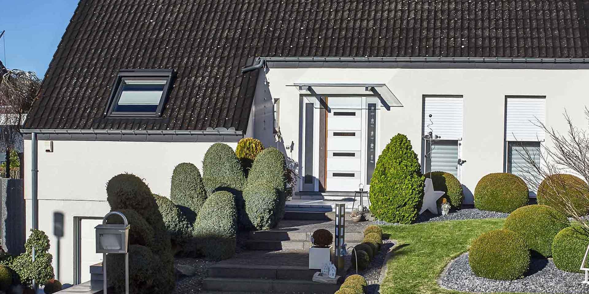 Weißes Einfamilienhaus mit einer weißen Coplaning Haustür und weißen Coplaning Alu Fenster.