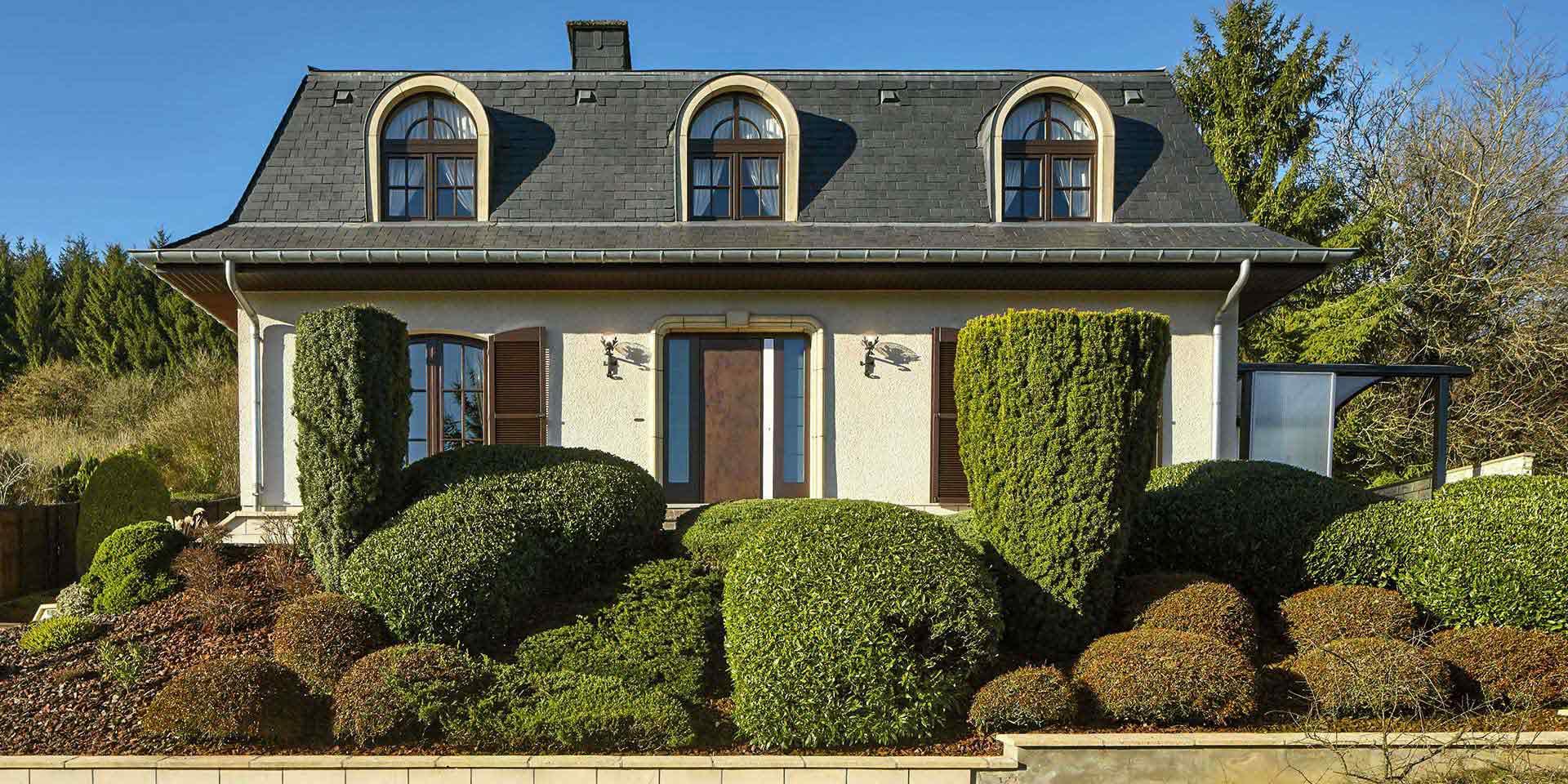 Gelbliches Einfamilienhaus mit edler brauner Coplaning Keramikhaustür.