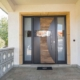 Nahaufnahme des Eingansbereich eines weißen Einfamilienhauses mit Blick auf eine moderne graue- Holz Coplaning Haustür.