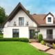 Vorderseite eines weißen Einfamilienhaus mit neuer moderner Coplaning Haustür und modernen Coplaning Alufenster.