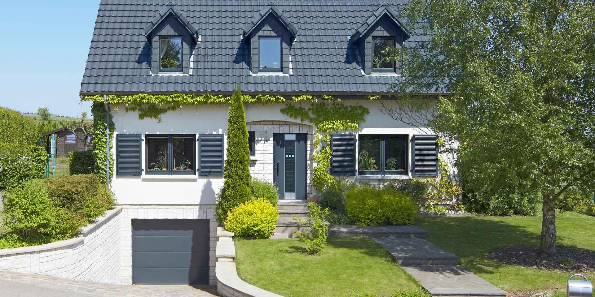Weißes Einfamilienhaus mit neuen modernen Haustür und grauen einbruchsicheren Coplaning Fenster und einem grauen Garagentor.