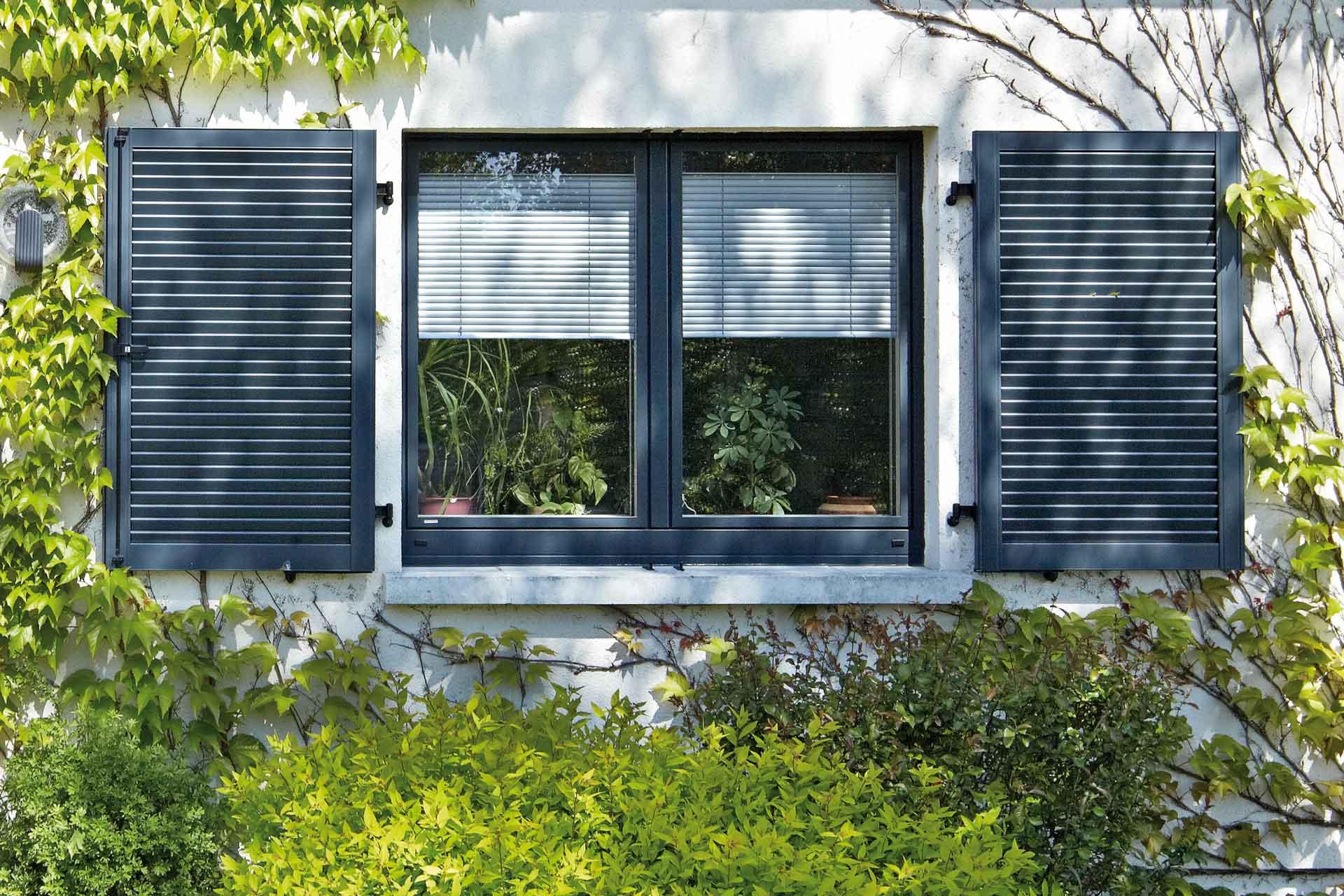 Nahaufnahme eines weißen Einfamilienhauses mit Blick auf ein graues modernes Holz- Alu Coplaning Fenster.