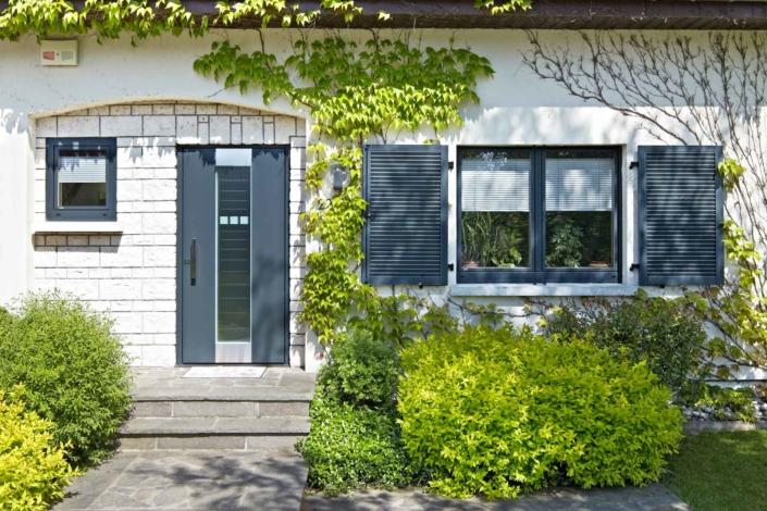 Nahaufnahme des Eingangsbereichs eines weißen Einfamilienhauses mit Blick auf die neue moderne graue Coplaning Haustür und jeweils links und rechts davon ein graues einbruchsicheres Coplaning Fenster.