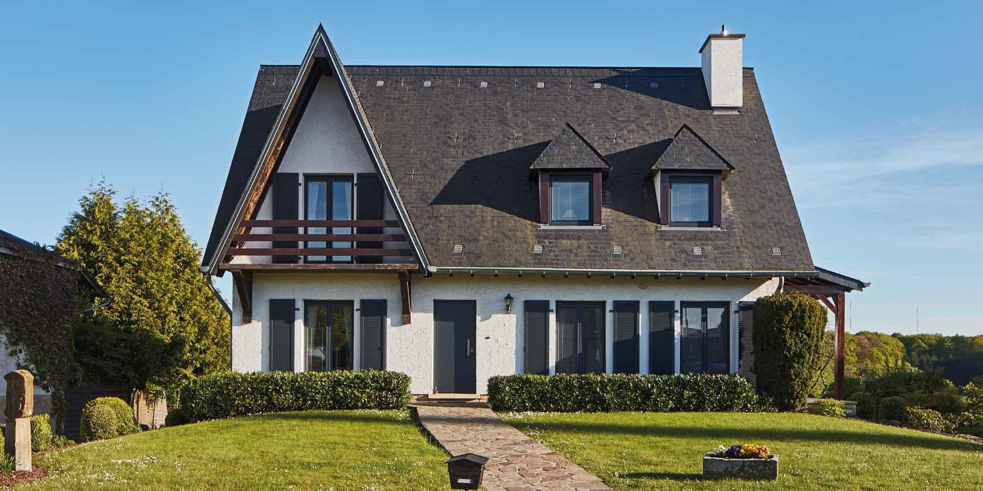 Weißes Einfamilienhaus mit einer grauen Coplaning Alu Haustür und grauen Coplaning Holz- Alu PVC Fenster mit passenden Klappläden.